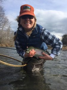 A happy female angler with a nice trout during a learn and fish outting.